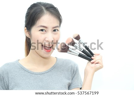 Young Asian woman holding brushes make up kits, isolated on white background - beauty makeup concept with copy space