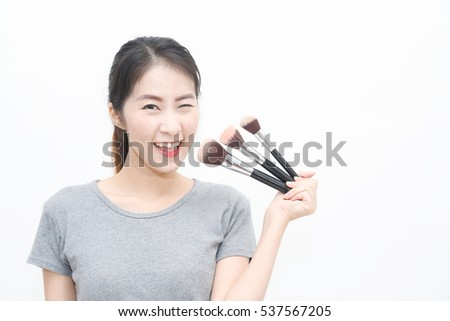 Young Asian woman holding brushes make up kits, isolated on white background - beauty makeup concept