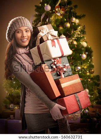 Young Asian woman holding Chrismtas presents and standing in front of a beautifully decorated Christmas tree. - stock photo