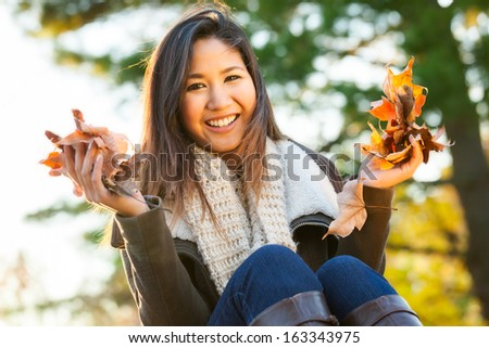 Young Asian woman holding dried leaves outdoors in the park in autumn - stock photo