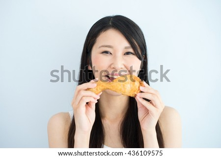 Young Asian woman holding fried chicken, against light blue background