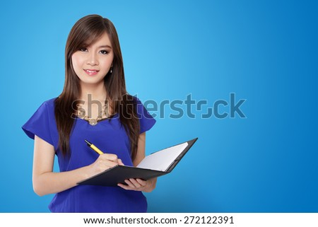 Young Asian woman holding pen and notebook, on vibrant blue background - stock photo