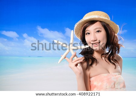 Young Asian woman holding starfish on the beach enjoy sunlight - stock photo