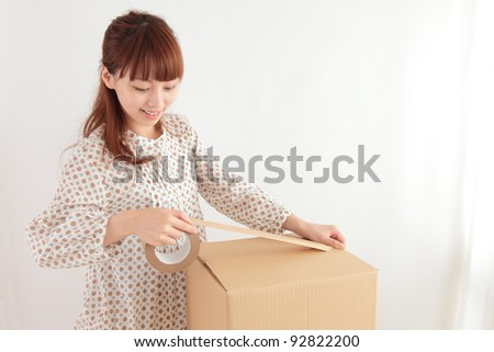 Young Asian woman in a cardboard packing - stock photo