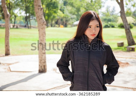 Young Asian woman in black sweat sport jacket in the park - stock photo