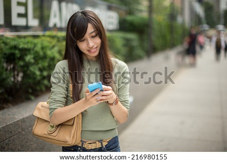Young Asian woman in city texting on a cellphone outdoor on a street