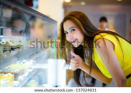 young Asian woman in front of sweet candy food store window - stock photo