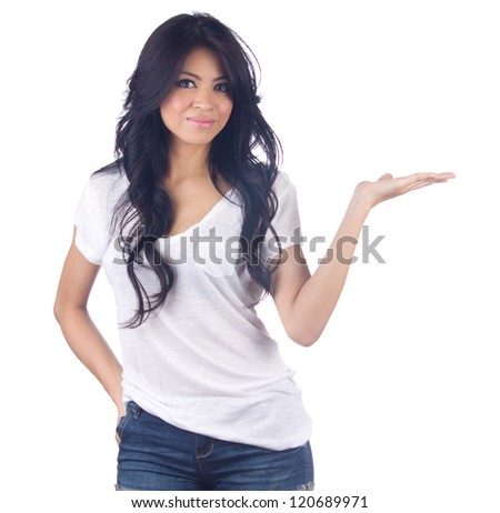 Young asian woman in jeans  showing something with open hand palm - stock photo