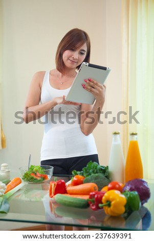 Young asian woman In Kitchen Following Recipe On Digital Tablet - stock photo