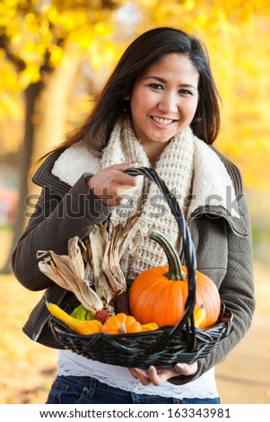 Young Asian woman in mid 20s carrying basket of pumpkins and gourds outside in the park in autumn - stock photo