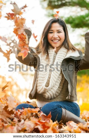 Young Asian woman in mid 20s playing in a pile of leaves at the park on an autumn day - stock photo