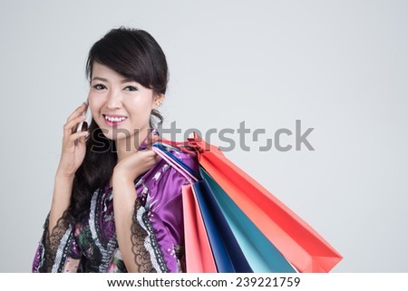Young asian woman in oriental purple dress with shopping bags.
