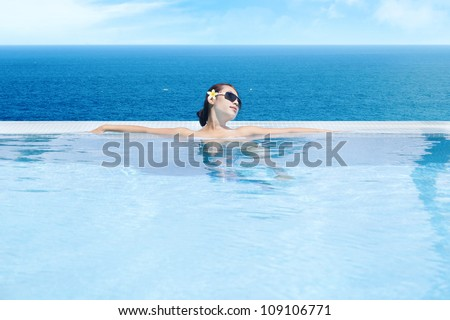 Young asian woman in the infinity pool enjoying the ocean view - stock photo