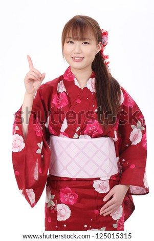 Young asian woman in traditional clothes of kimono, pointing up - stock photo