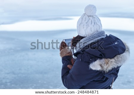 Young Asian woman in winter clothes seen from behind as she checks a photo on her smartphone in front of a frozen lake. - stock photo