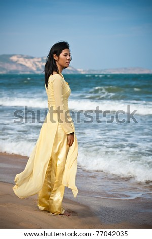 Young Asian Woman in yellow ao dai on the Beach - stock photo