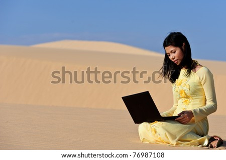 Young Asian woman in Yellow Ao Dai with a laptop in the dunes i - stock photo