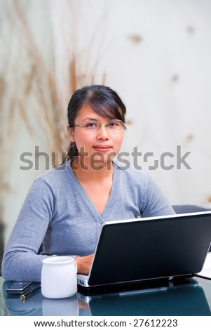 Young Asian woman is working at home and smiling to the camera
