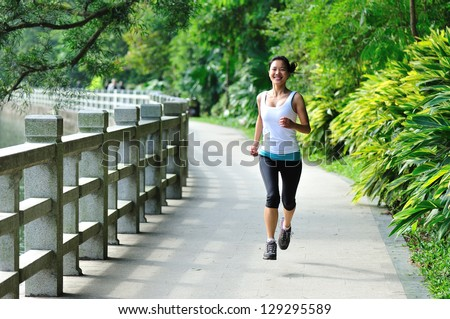 young asian woman jogging in park - stock photo