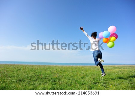 young asian woman jumping on green grassland with colored balloons  - stock photo