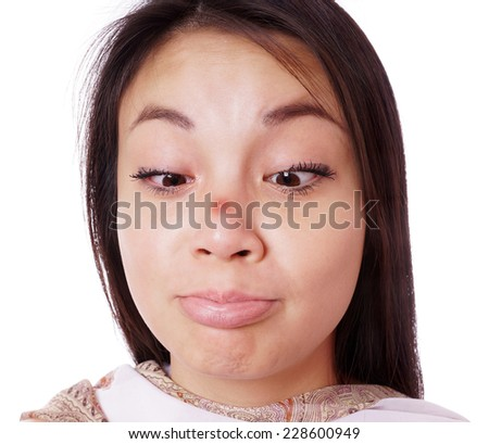 young asian woman looking cross-eyed at red pimple on her nose - stock photo