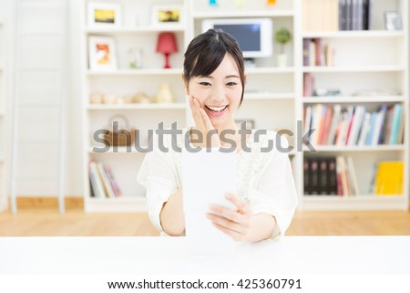 young asian woman looking mirror in the room - stock photo