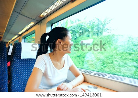 young asian woman looking out of the window smiling interior of train/subway  - stock photo