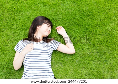 young asian woman lying on the lawn - stock photo