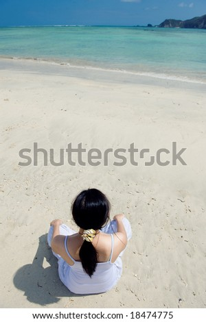 young asian woman meditating on the beach - stock photo