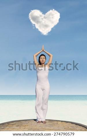 Young asian woman meditating under love cloud at beach. - stock photo