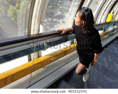Young asian woman on elevator looking out - stock photo