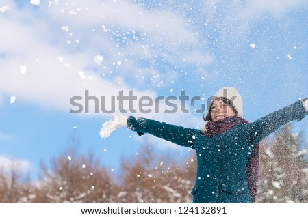 Young Asian woman playing in the snow - stock photo