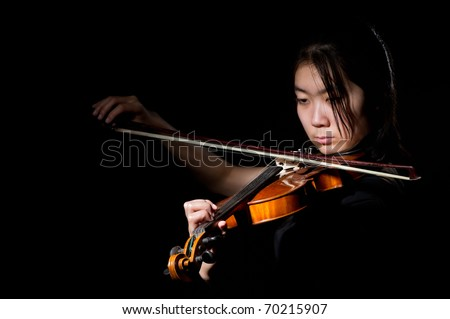 young asian woman playing violin on black background - stock photo