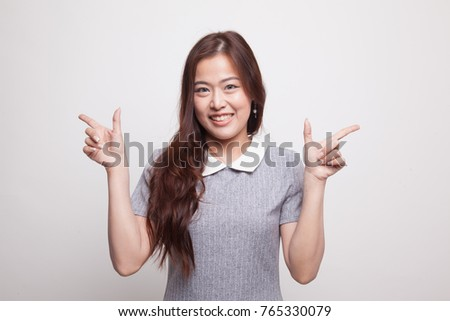 Young Asian woman point to left and right on gray background