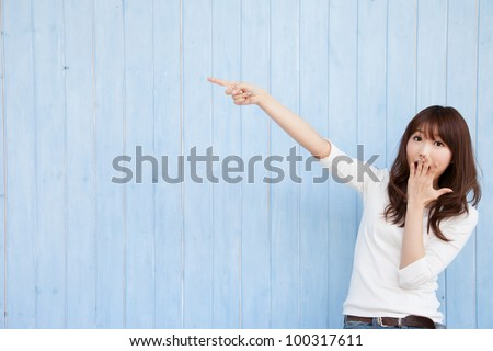 Young Asian woman pointing at a blue background - stock photo