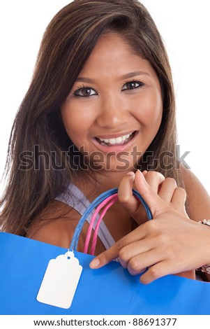 Young Asian woman pointing to a blank tag on a shopping bag - stock photo