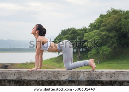Young asian woman posing yoga, do the exercise for relax, healthy and control mind  in beautiful mountain and lake background, morning time.