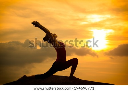 Young asian woman practicing yoga warrior pose at sunset - stock photo