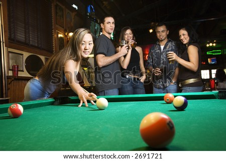 Young asian woman preparing to hit pool ball while playing billiards. - stock photo