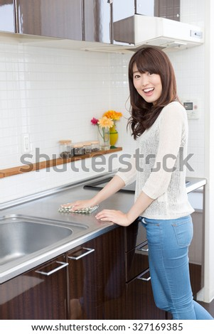 young asian woman relaxing in the kitchen - stock photo