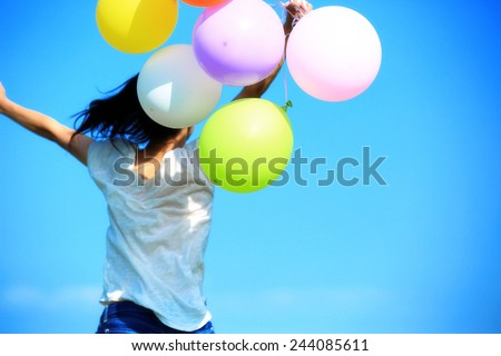 young asian woman running and jumping under blue sky with colored balloons  - stock photo