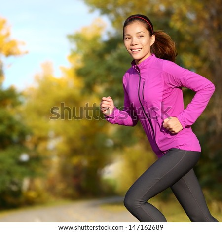 Young Asian woman running female jogger happy. Female runner jogging in park in autumn park forest in fall colors. Beautiful young sport model. Multi-ethnic Asian Chinese / Caucasian girl in her 20s. - stock photo