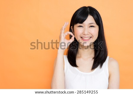 young Asian woman showing OK gesture against orange background - stock photo