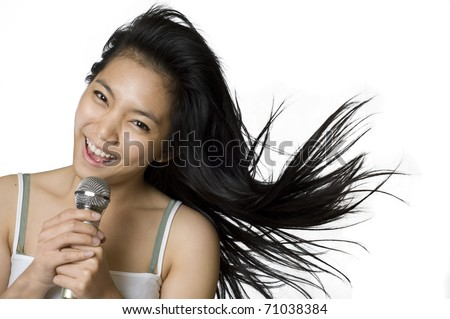 Young Asian woman singing into a microphone