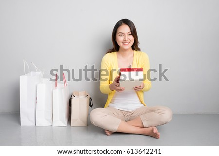 Young asian woman sitting besides row of shopping bags holding red gift box