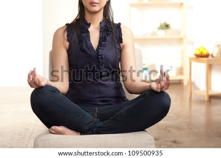 Young Asian woman sitting crossed legged in a meditation posture. - stock photo