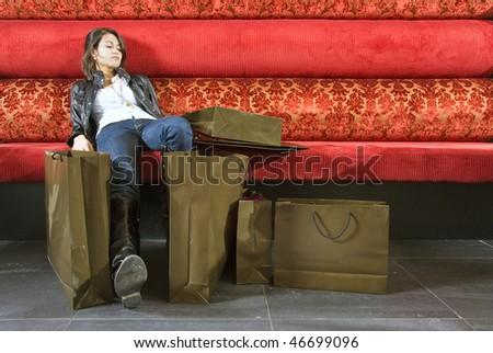 Young asian woman sitting on a padded couch tired from shopping - stock photo