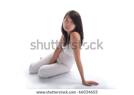 young asian woman sitting on a white background in white looking at the camera - stock photo
