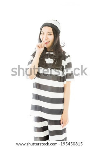 Young Asian woman smiling in prisoners uniform with finger in mouth - stock photo