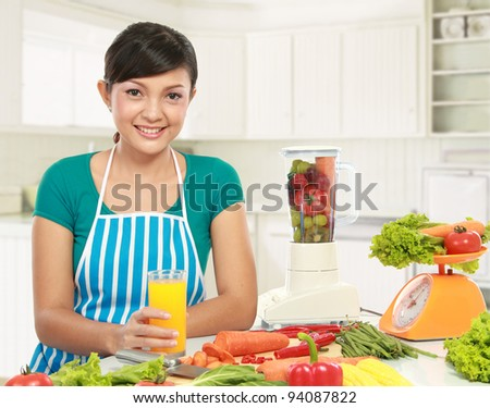 young asian woman smiling while having a glass of fresh juice in the kitchen